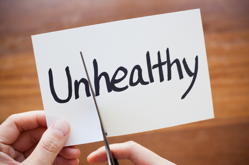 Close-up of hand using scissors cutting the word on paper, Unhealthy become Healthy.
